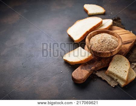 Bowl of breadcrumbs and slices of a loaf. Selective focus