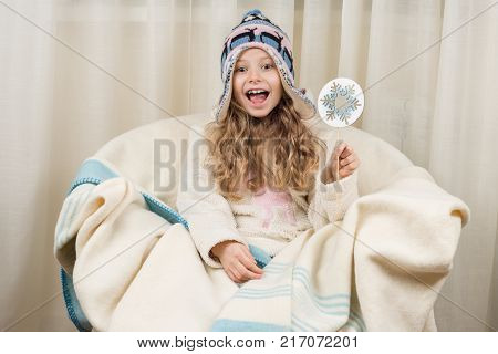 Emotional girl child in winter hat and sweater concept of winter days. A girl in an orthodontic plate.