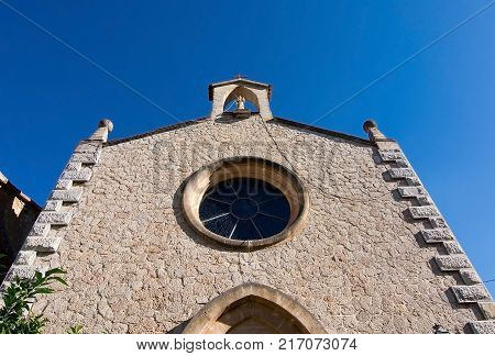 MALLORCA, BALEARIC ISLANDS, SPAIN - OCTOBER 26, 2017: Church facade with rosary window on a sunny day on October 26, 2017 in Mallorca, Balearic islands, Spain.