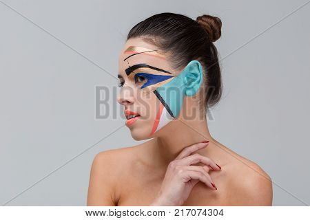 Close-up portrait of a brunette, in the studio, with bare shoulders, with bright geometric make-up, blue ear, make-up concept, girl looks away, hand holds at the neck.