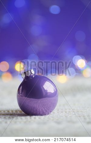 Lilac Christmas Ball On White Knitted Fabric On Purple Background With Warm Bokeh