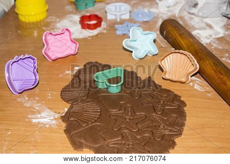 Gingerbread cookies preparation. Christmas cookies baking on wooden background. Christmas decorations, gingerbread cookie dough, cookie cutters, spices, oranges and fir tree frame. Top view