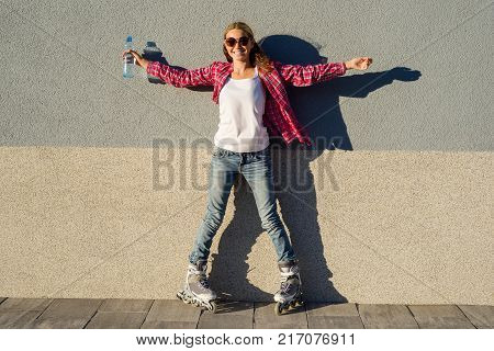 A beauty teen model girl, shod in rollerblades holding a water bottle. Sports, health and active leisure.