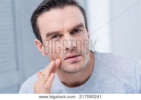 Strange rush. Concerned earnest unhappy man looking at the camera and scrutinizing his face while touching face with a finger