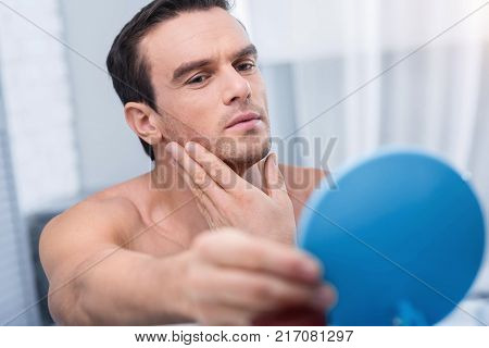 Ideal face. Irresistible young good looking man holding blue mirror and looking at it  while caressing his chin