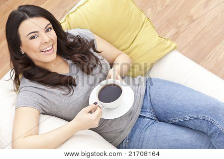 A beautiful young Latina Hispanic woman or girl with a wonderful toothy smile drinking black tea or coffee from a white cup at home