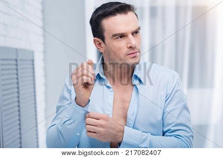 Office shirt. Irresistible good looking interesting man looking aside while  fastening cuffs and standing on the light background