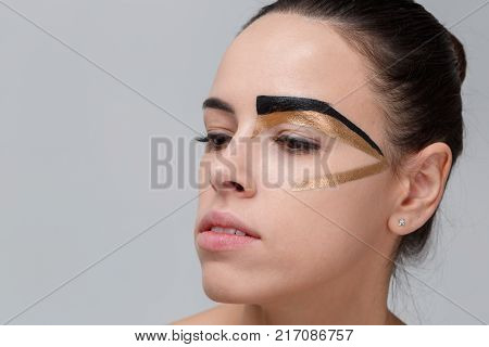 Close-up portrait of a girl, on a gray background in the studio, with one painted eyebrows to the ear, black, golden shadows, geometric make-up, eyes closed. The concept of makeup.