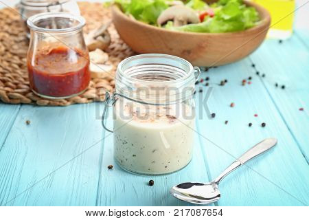 Glass jar with ranch salad dressing on table