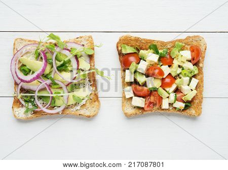 Two avocado toasts with mashed avocado and onionsliced avocado tomato snow pea sprouts and goat cheese on white wooden background