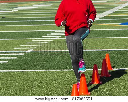 A high school girl track and field athlete doing speed drills by steping over orange cones on a green turf field.