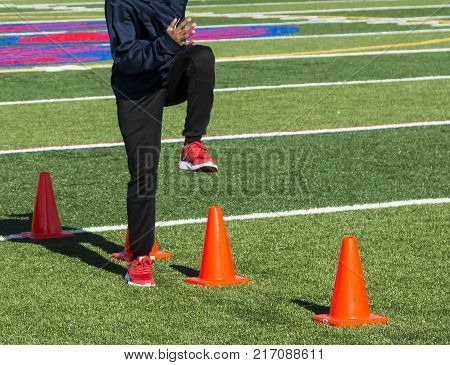 A high school teenager steps over orange cones and drives his foot down to the turf during track and field practice.
