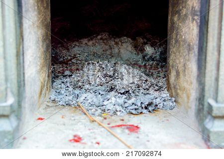 Ash and charred firewood in a fireplace, after burnt.