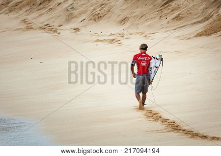 SUNSET BEACH HAWAII USA - DECEMBER 2, 2017: Pro surfer walking down the beach at the 2017 Vans World Cup of Surfing competition at Sunset Beach on Oahu's scenic North Shore. This is the second of three surfing competitions and Conner Coffin.