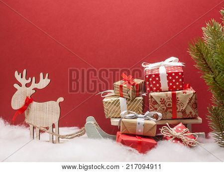 christmas deer with sledges and pile of presents red background