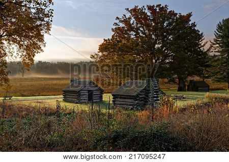 A misty morning at Valley Forge National Historic Park located in Valley Forge Pennsylvania USA. The buildings are reproductions of cabins used by Revolutionary War soldiers during the winter of 1777-78 under the command of George Washington.