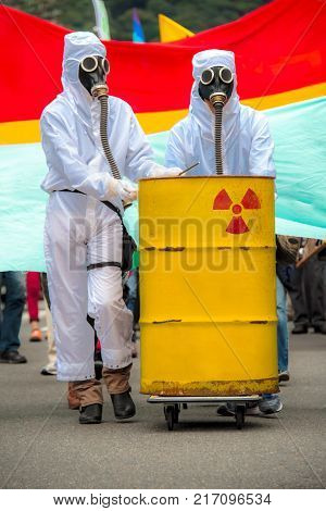 Two men in bio-hazard suits standing behind a rusty tank with nuclear symbol screened on. They are wearing a gas masks with flexible rubber breathing tubes.