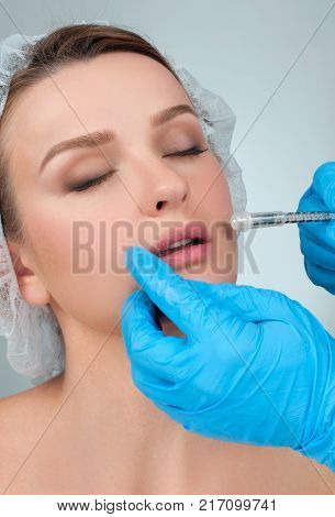 Beautiful girl receiving filler injection in lips. Cosmetic Treatment. Plastic Surgery. poster