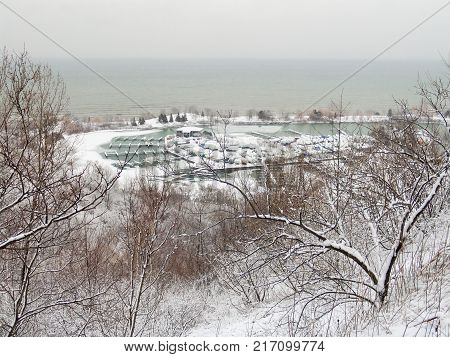 View through snowy trees from the Scarborough Bluffs to marine and boats in snow winter. Ontario Lake Toronto Canada