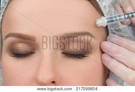 Woman is getting filler injection over eyebrow. Anti-aging treatment and face lift. Cosmetic Treatment. Facial skin lifting injection to woman's face. Plastic Surgery