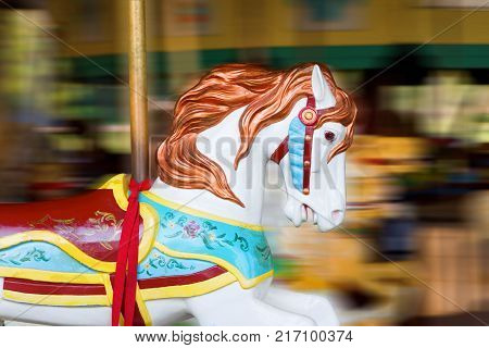 A white merry go round horse in motion