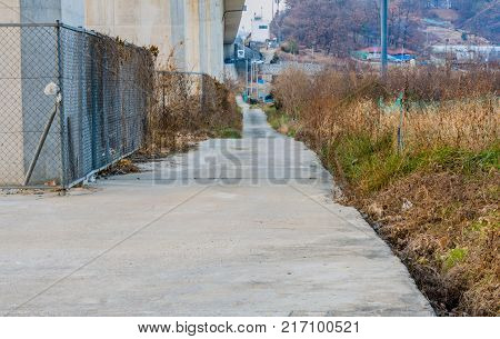 Narrow concrete roadway running along side an overpass with chain link fences on one side and tall grass and trees on the other leading to a small community in the background