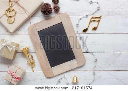 Table top view aerial image of music note & decoration merry Christmas & Happy new year background concept.Blackboard and gift tree with items for winter season on vintage white wooden at home office.
