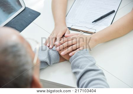 Close up on hands. Young Asian Female doctor reassuring senior male patient with holding hands in medical office.
