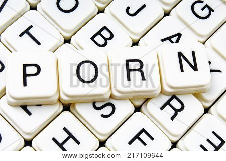 Porn text word crossword. Alphabet letter blocks game texture background. White alphabetical cubes blocks letters on crossword letters educational toy background. Porn title.