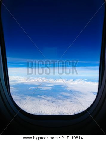 The beautiful blue sky and cloud , take a photo on the window of airplane with hight flight. Good travel with the plane.