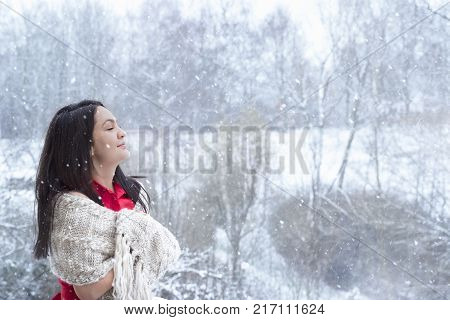 Brunette woman enjoying the snowfall - Attractive young woman with long dark hair in a red dress covered by a handmade shawl with her eyes closed enjoying the snowfall.