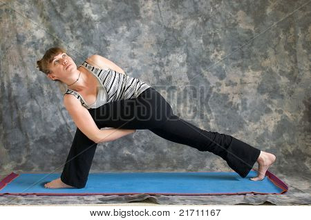 Young woman on yoga mat Yoga posture Parsvakonasana or bound Extended Side Angle pose against a grey background facing left lit by diffused sunlight. poster