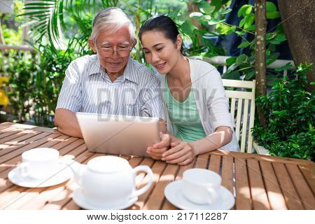 Smiling woman and her senior father watching videos on digital tablet