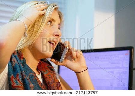 Beautiful smiling businesswoman or secretary in the workplace calling on smartphone at office. business technology communication and people concept