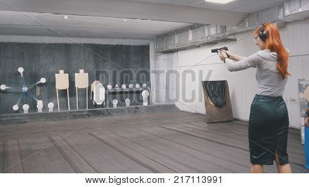 Woman with red hair shooting with a gun in shooting gallery, horizontal