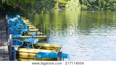 Old catamarans parked near a wooden pier.