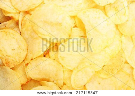 Chips pattern. Yellow salted potato chips as background. Chips texture studio photo Food photo.