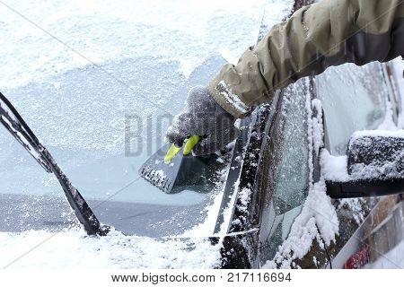 hand is scraping a wind screen of a car