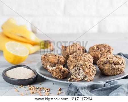 Close-up view of healthy gluten-free homemmade banana muffins with buckwheat flour. Vegan muffins with poppy seeds on gray plate over gray wooden table. Copy space