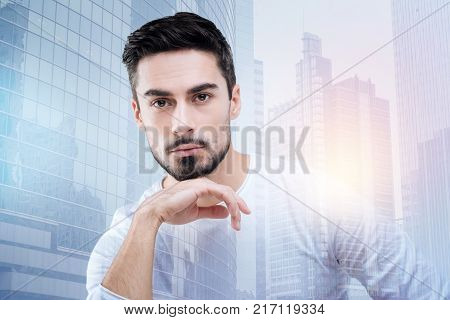 Smart glance. Handsome bearded calm student sitting at the lecture with his head resting on his hand and being attentive while looking at his teacher