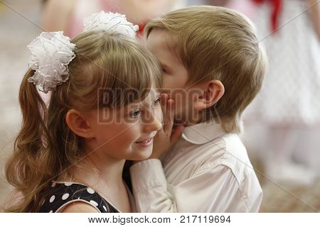 Belarus the city of Gomel 26.05.2016. Graduation kindergarten.The boy whispers the secret girl in the ear.Tell a secret.