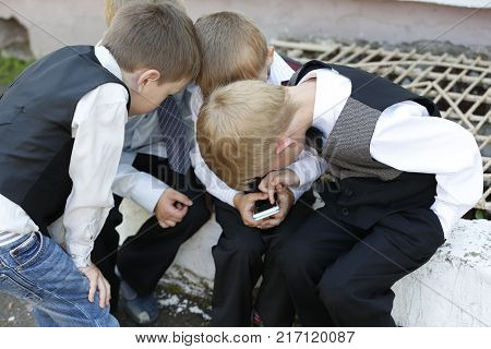 Belarus the city of Gomel 03.06.2016. Graduation kindergarten.Children are watching a mobile phone.Mobile phone and children.Influence of cellular communication on children