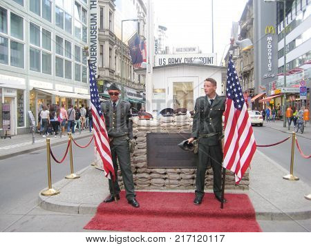 BERLIN, GERMANY - JULY 20, 2016: Checkpoint Charlie U.S. Army Historic Memorial with American Soldiers. Famous Berlin Wall Crossing Point Between East and West Parts of Berlin City During Cold War.