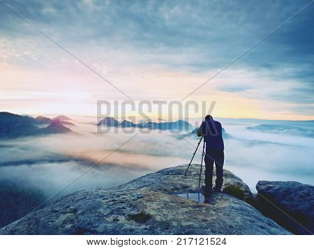 Photo artist in work. Photographer in rocky mountains. Traveller takes photos of dreamy majestic landscape sunset at horizon
