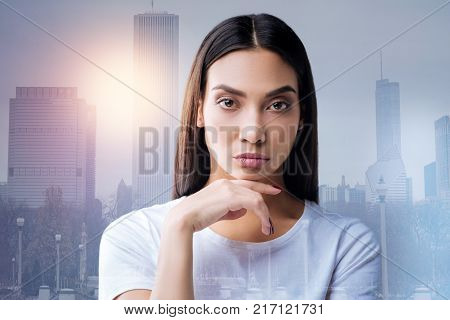 Attentive listener. Serious qualified smart psychologist looking attentive while being at work and listening to her new worried client