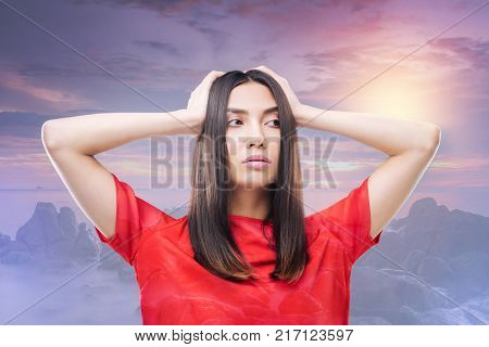 New outlook. Clever emotional fashionable woman standing with her hands on her head and thoughtfully looking into the distance while considering the changes in her outlook poster