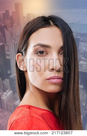 Confident glance. Clever experienced educated businesswoman standing against the urban background and looking confident before having an important meeting with her business partner