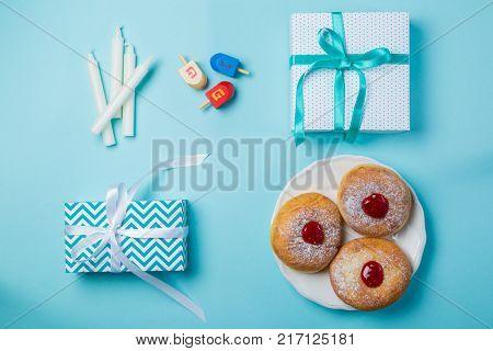 Symbols of hanukkah - sufganiyah, presents, candles, dreidel on blue background