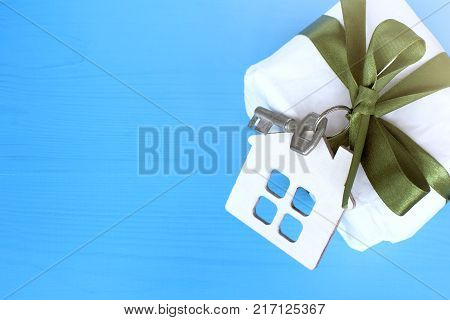 layout houses with key tied with green bow to gift on blue wooden background top view / complete refurbishment as gift