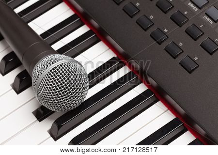 Microphone Laying on Electronic Synthesizer Keyboard Abstract.